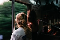 two person standing on train window