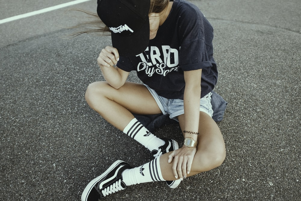 woman wearing black and white crew-neck shirt and gray shorts on gray concrete ground