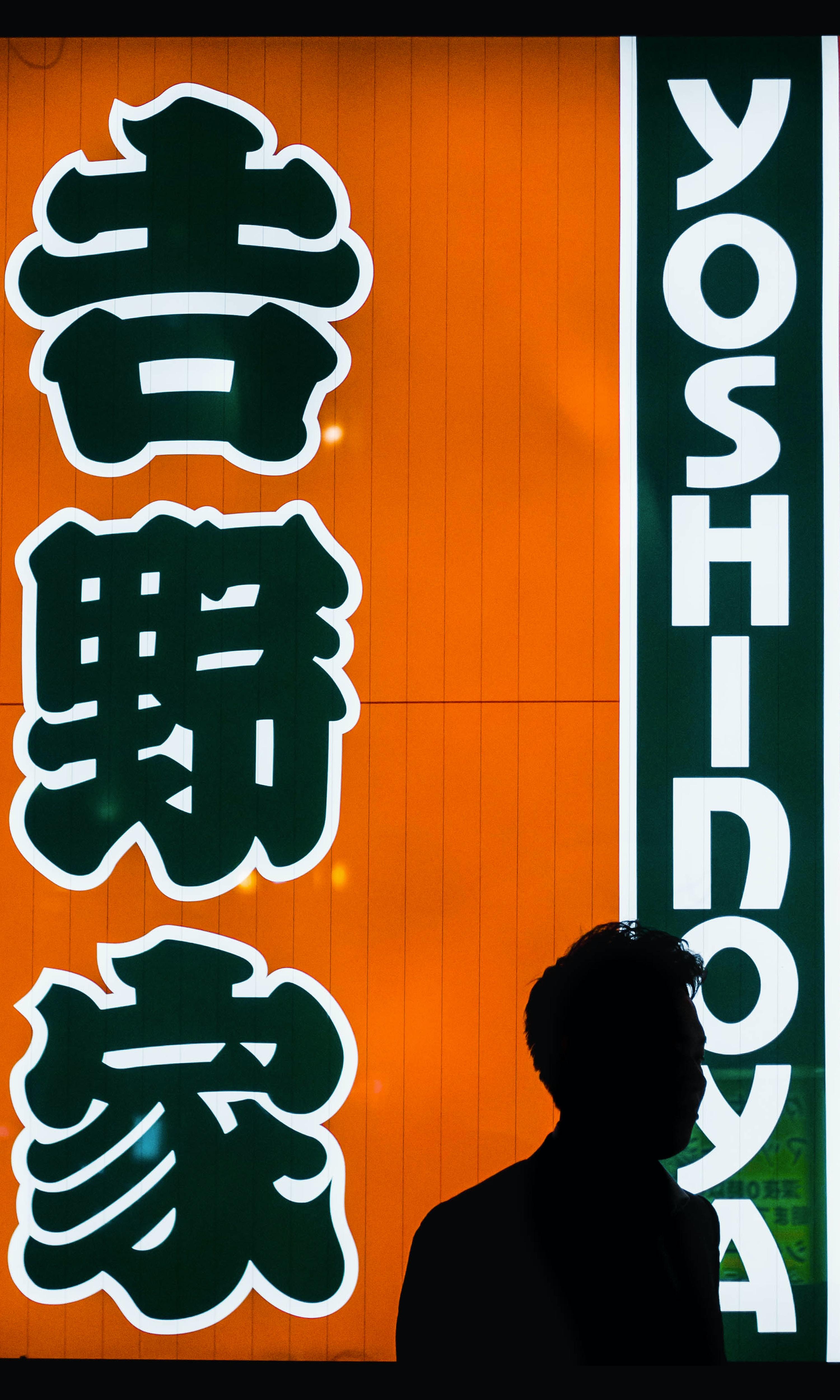 man standing near Yoshinoya store facade