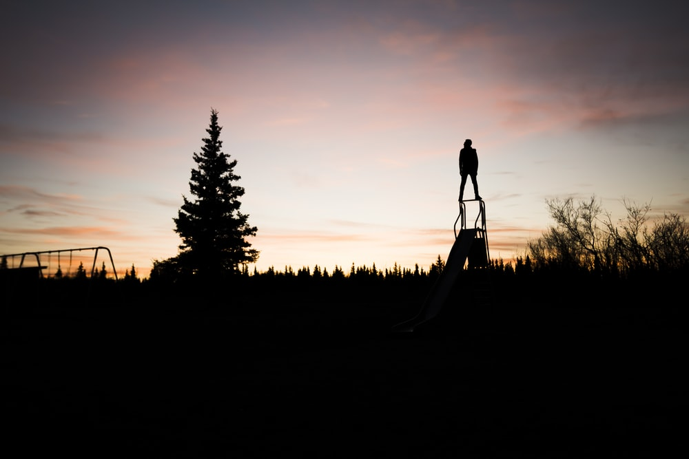 silhouette of person standing on slide during sunset