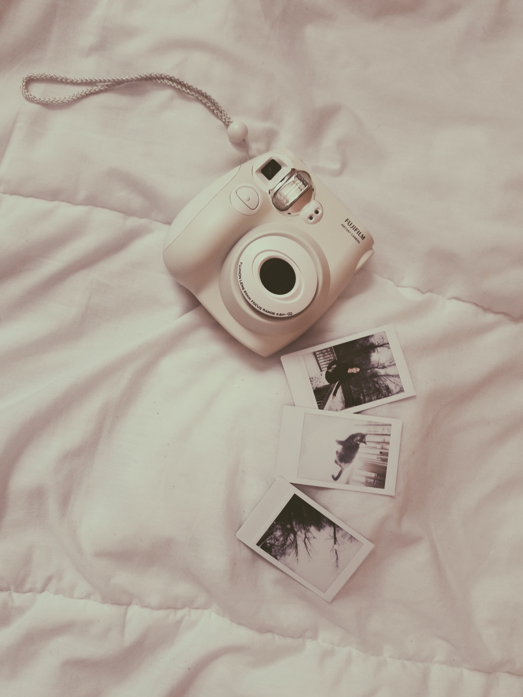 white Fujifilm instant camera on white comforter