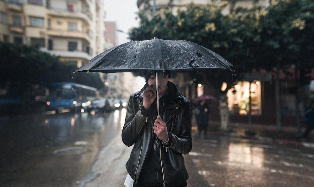 man carrying umbrella