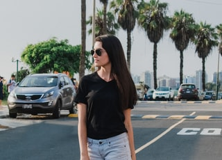 woman wearing black V-neck shirt and blue shorts standing on gray concrete road