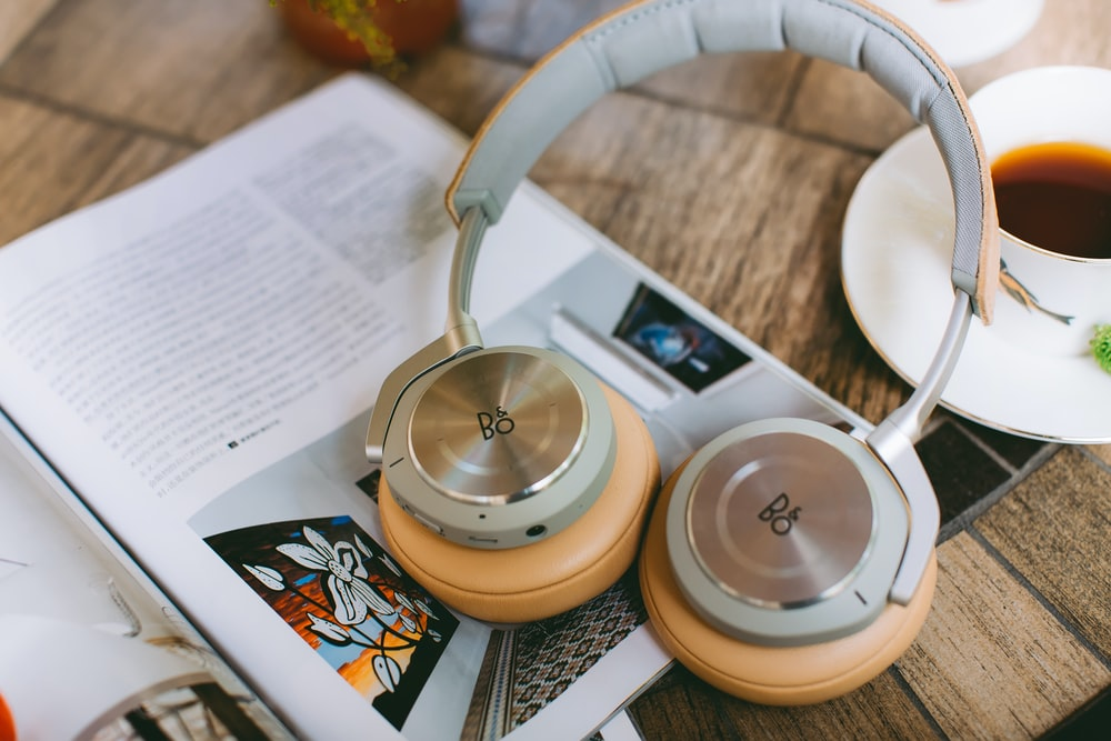 gray and yellow on-ear headphones beside white ceramic cup