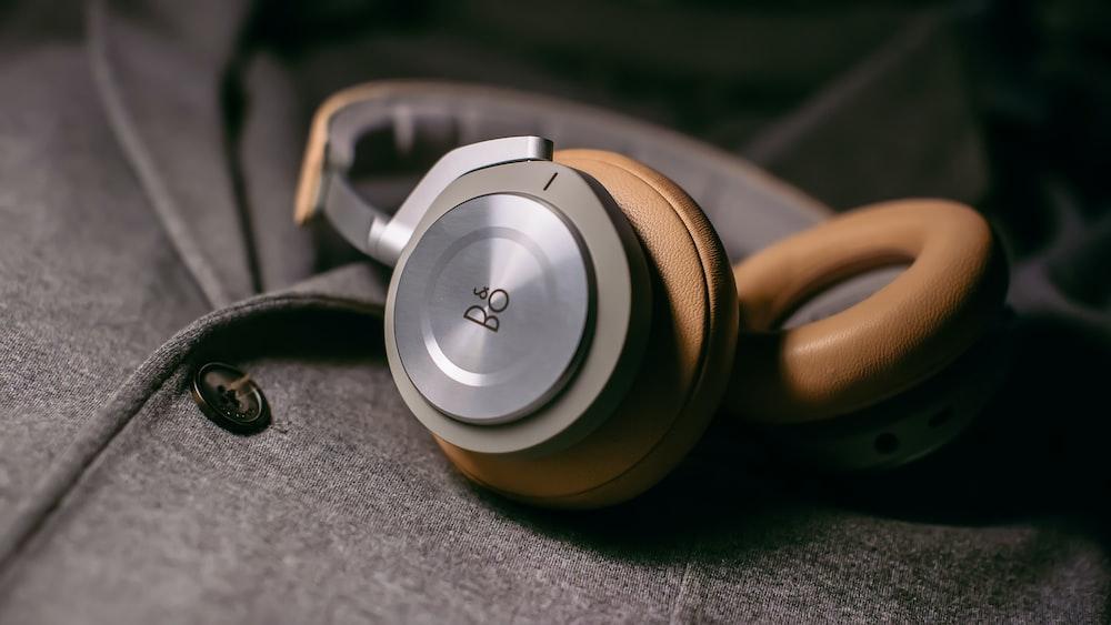 closeup photo of gray corded headphones on gray fabric sheet