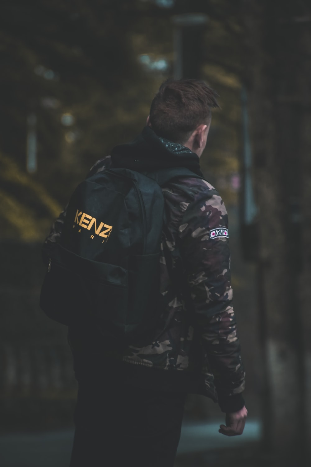 man wearing camouflage jacket and backpack