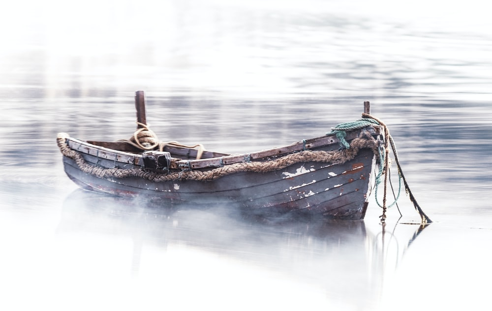 empty brown boat on body of water