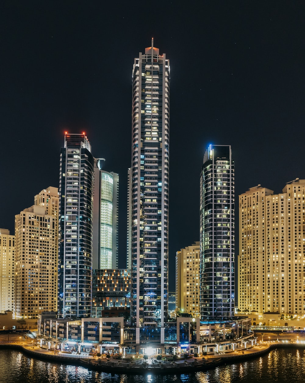 three lighted high-rise buildings near body of water