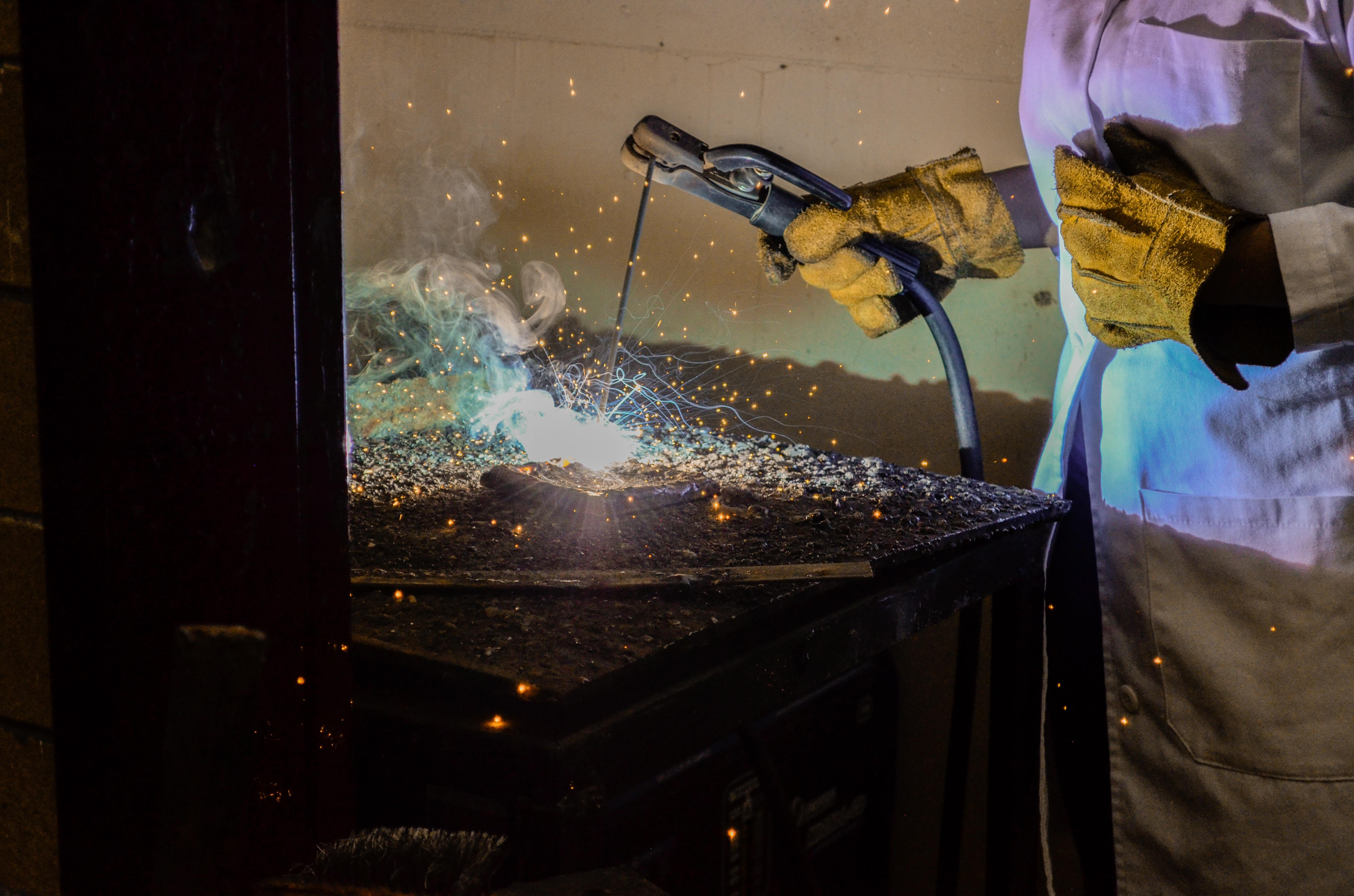 person welding metal using electrode holder