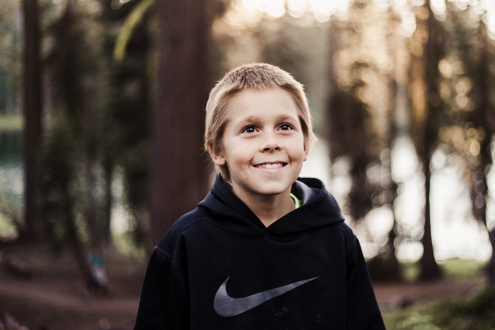 close-up photography of boy in black Nike pullover smiling