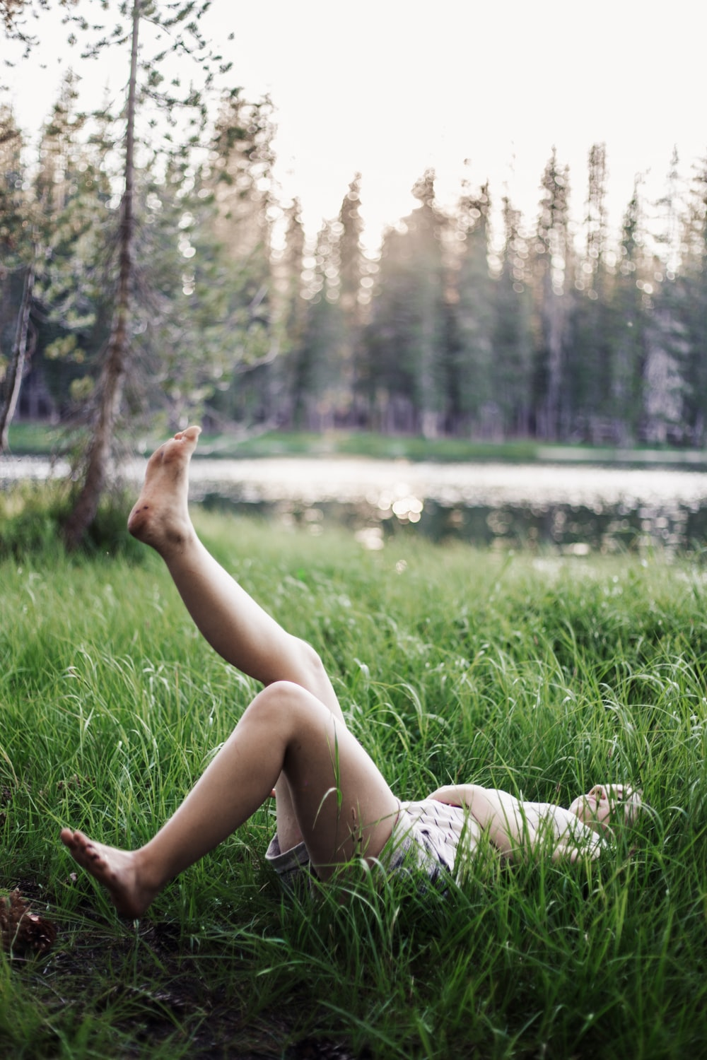 girl laying on green grass field