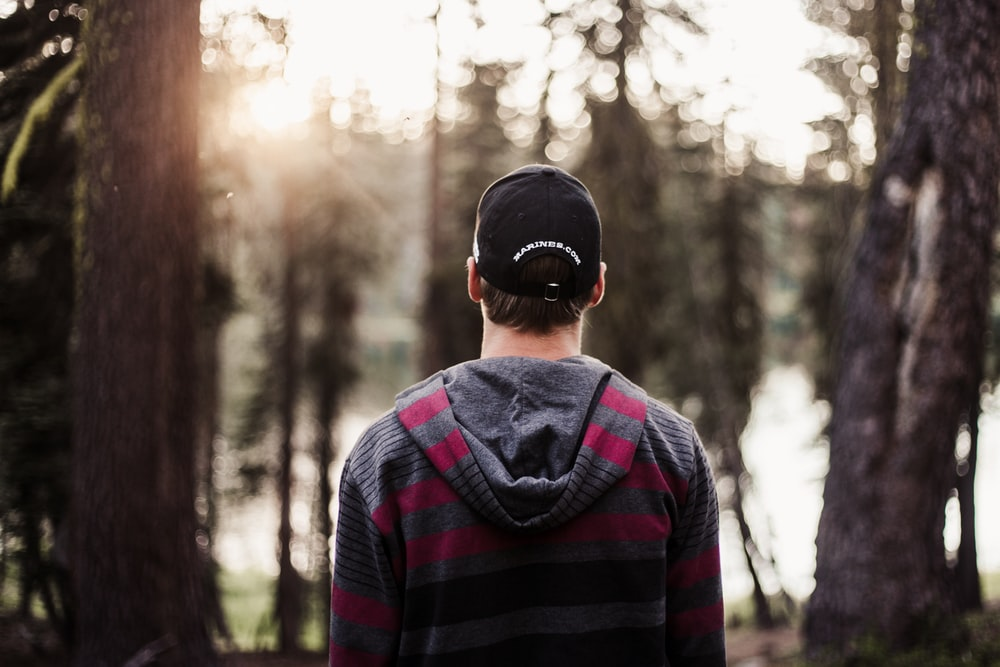 selective focus photo of man standing front of trees at daytime