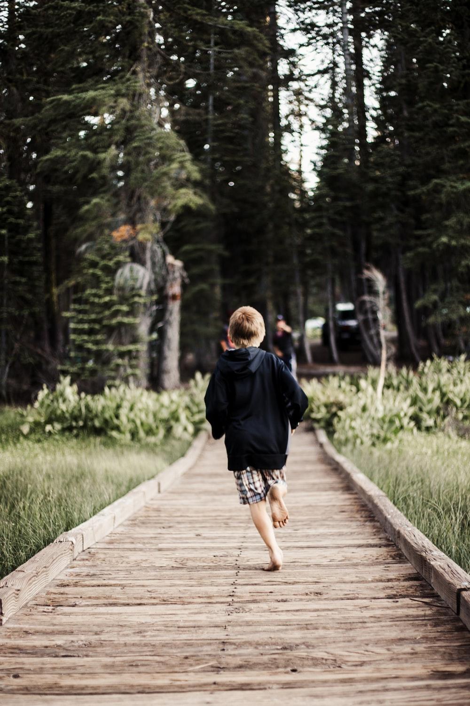 toddler running on brown wooden pathway