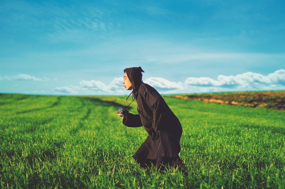 photography of man in black cloak running on grass field