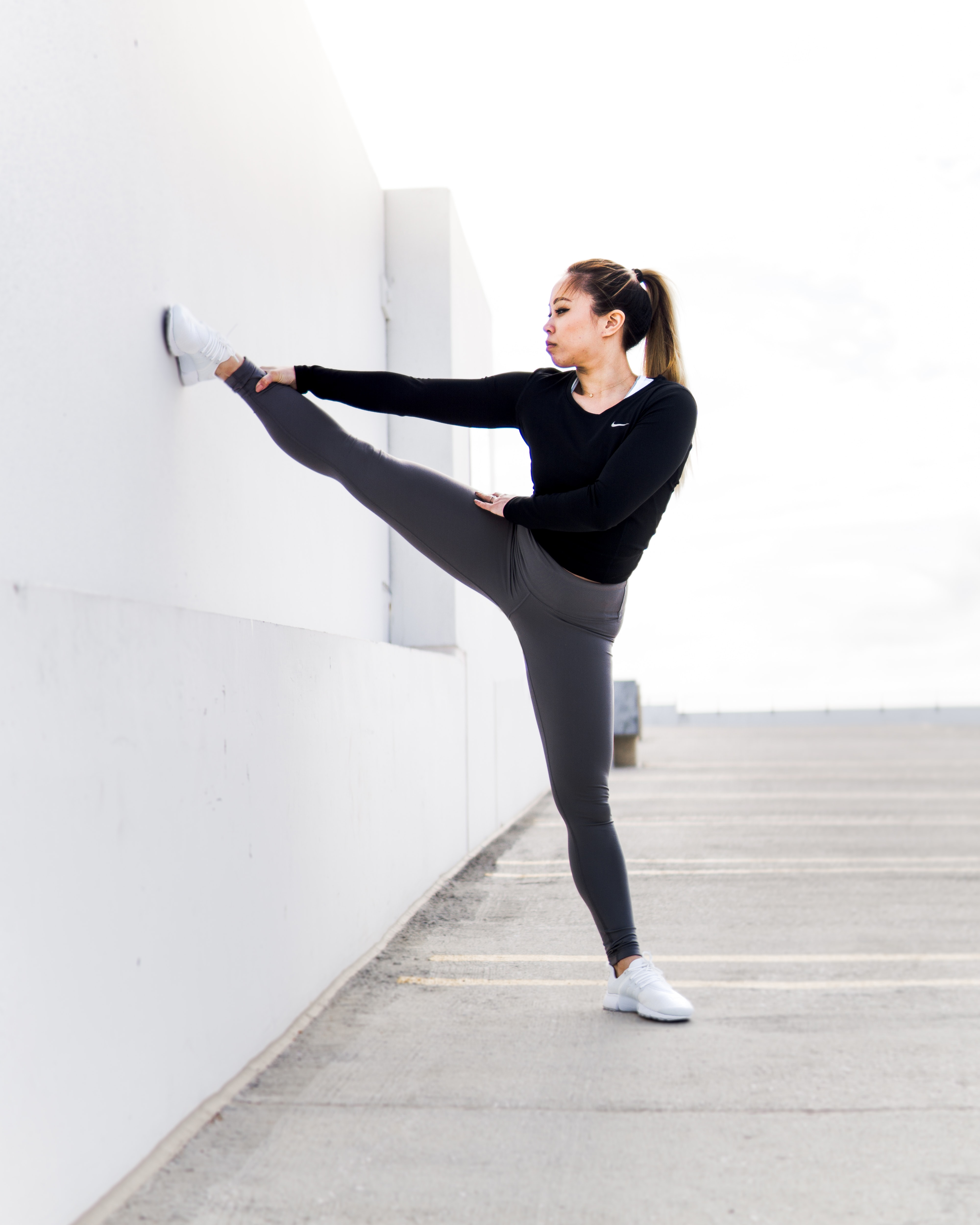woman stretching on white wall