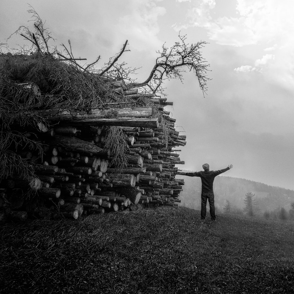 grayscale photography of man standing next to piles of woods