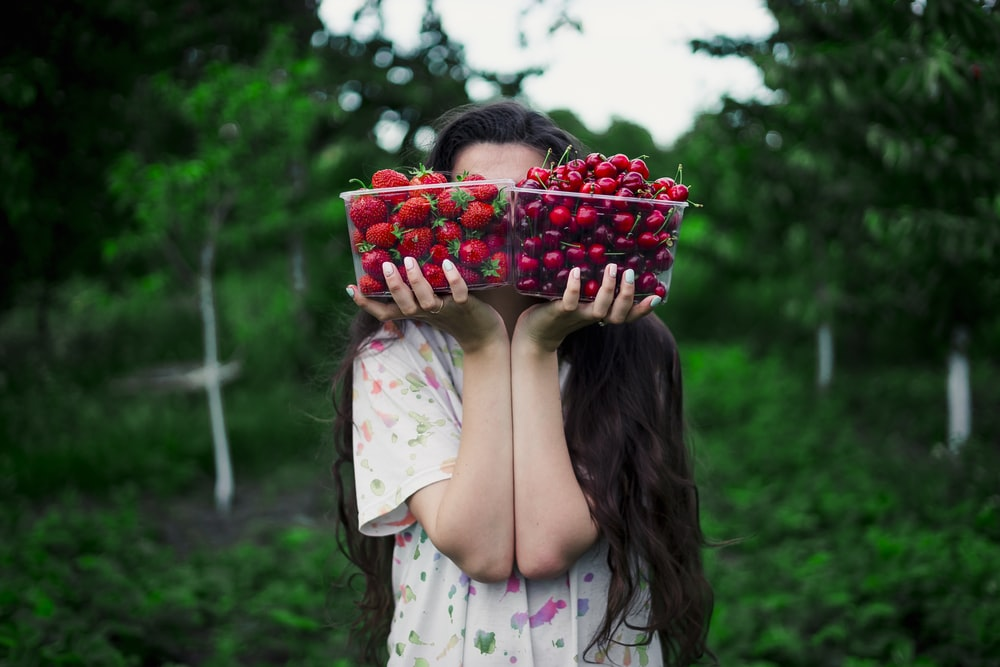 woman holding two bowls of straberries