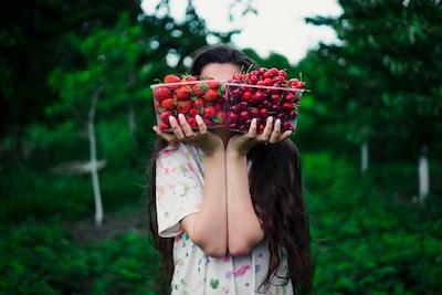 果物を両手で持って顔を隠している女性