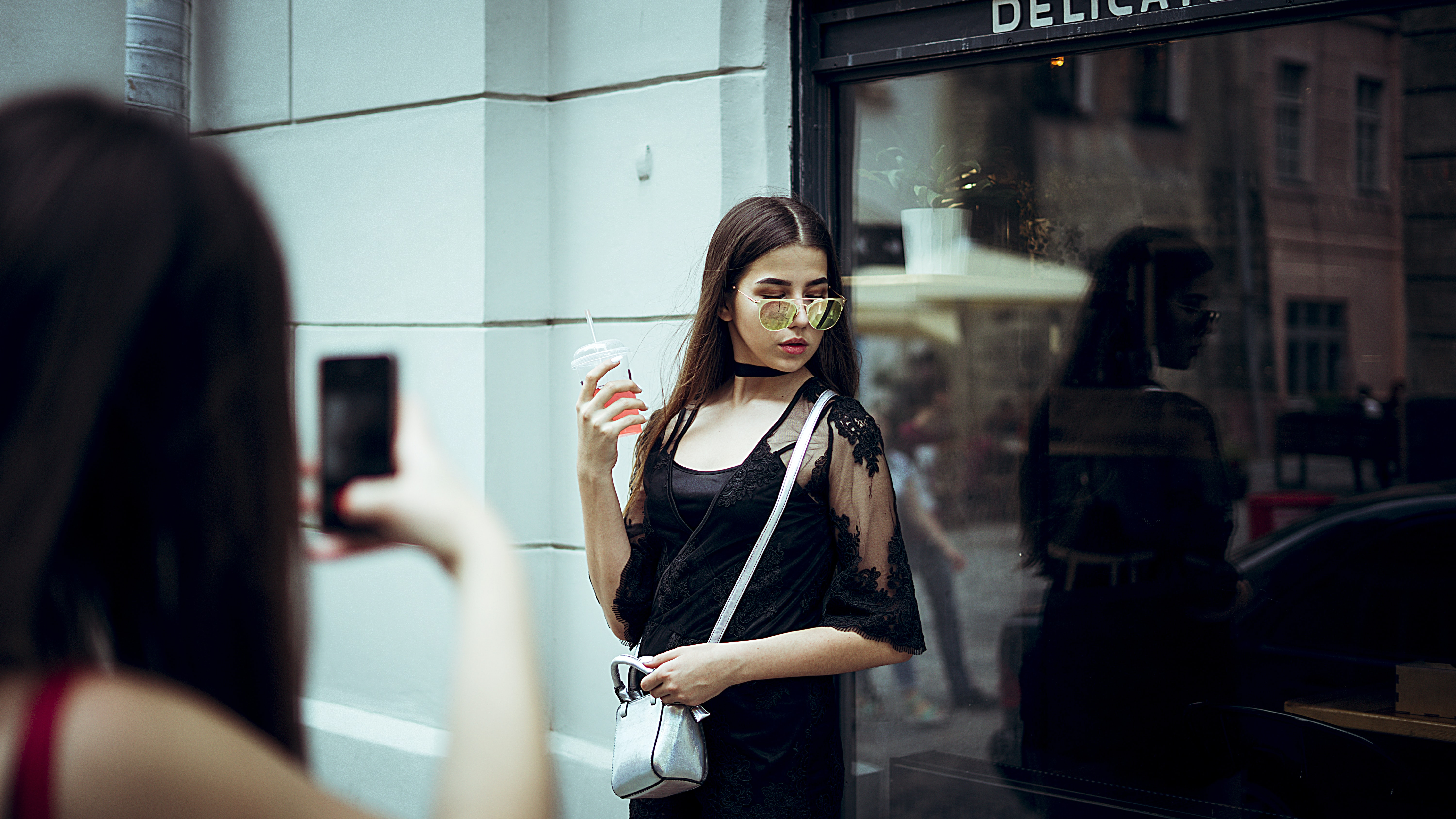 woman taking photo of woman carrying sling bag