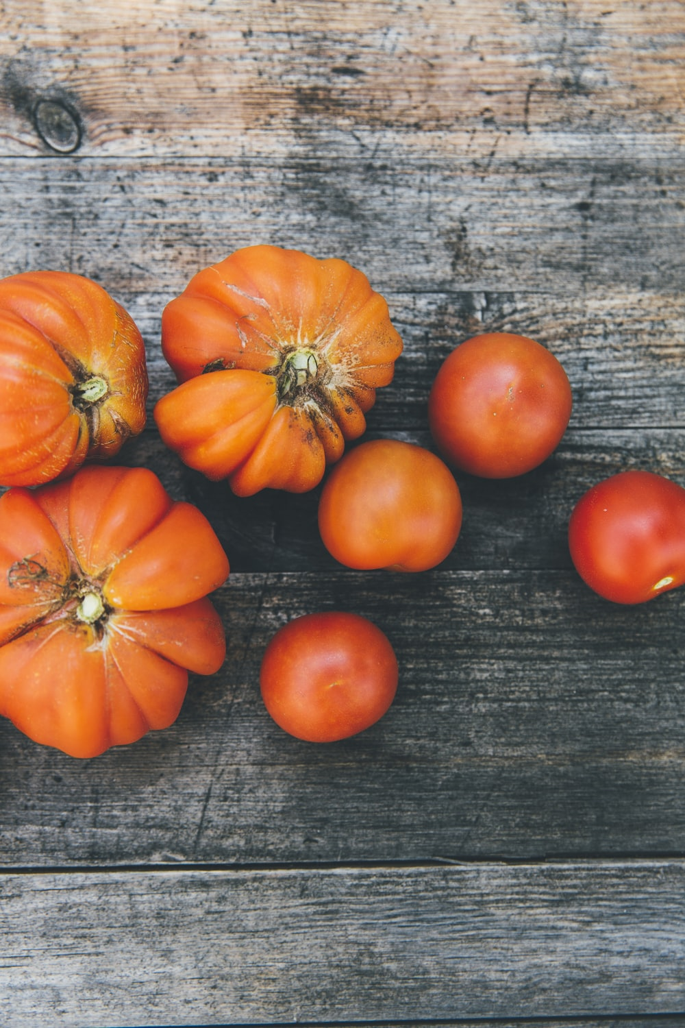 four red tomatoes and three orange fruits