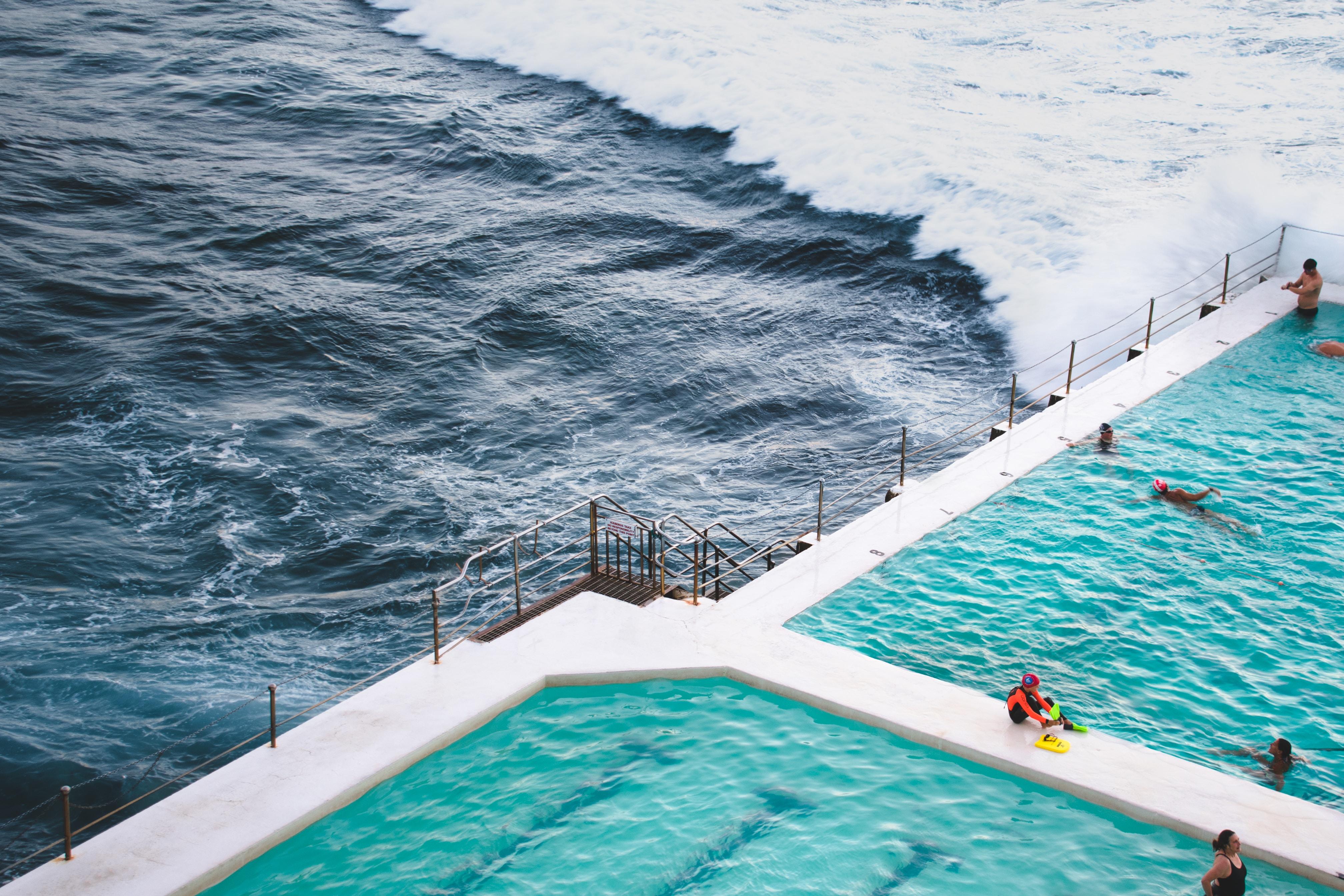 people swimming in pool near sea during daytime
