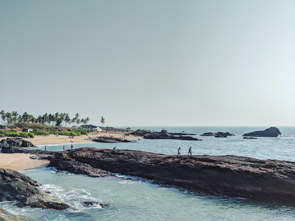 people walking on large rock monolith near sea