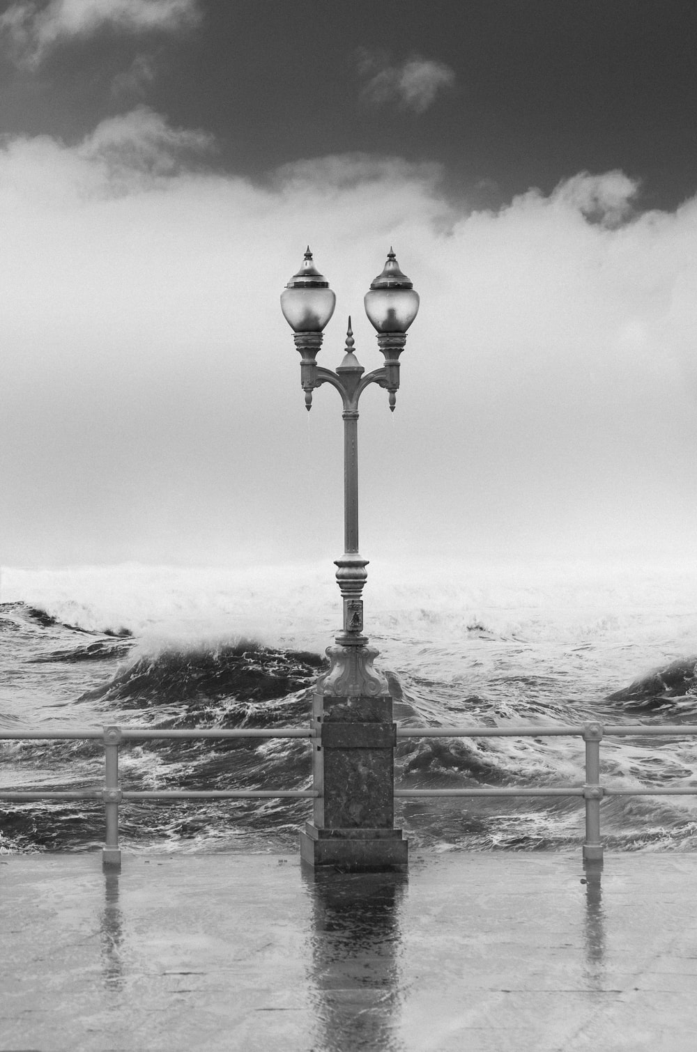 grayscale photography of outdoor lamp near sea