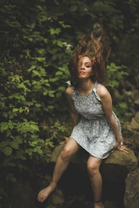 woman banging her hair on mid air while sitting on stone
