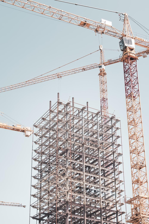 gray metal building frame near tower crane during daytime