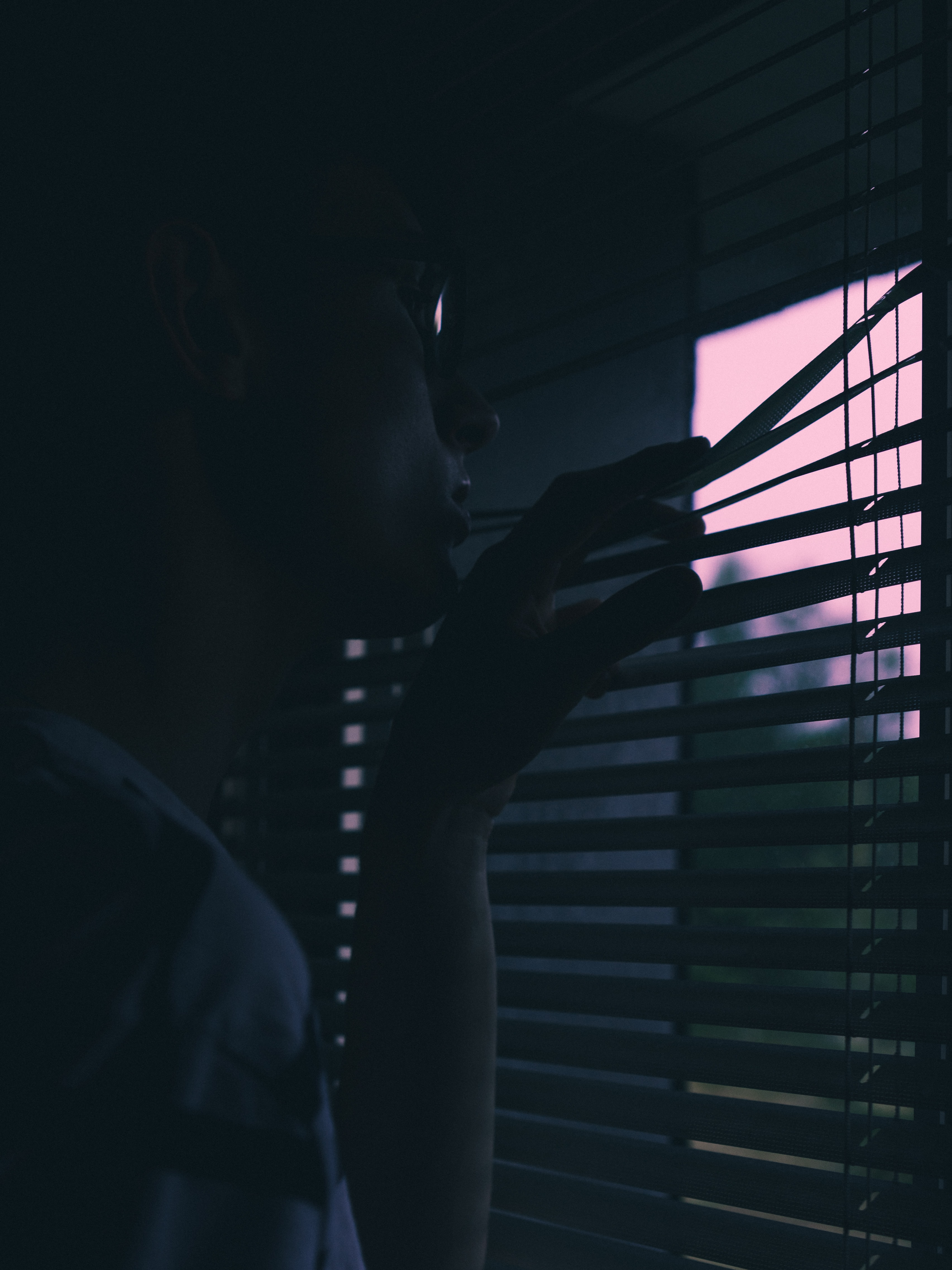 person looking through window blinds