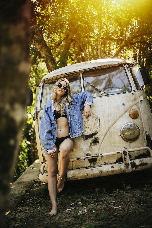 woman leaning on beige Volkswagen Samba