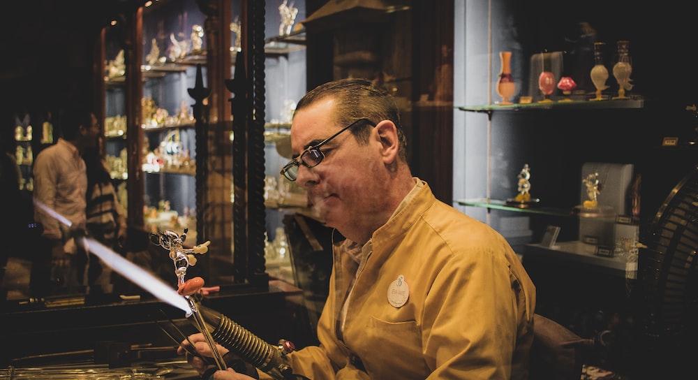 man making figurine inside room