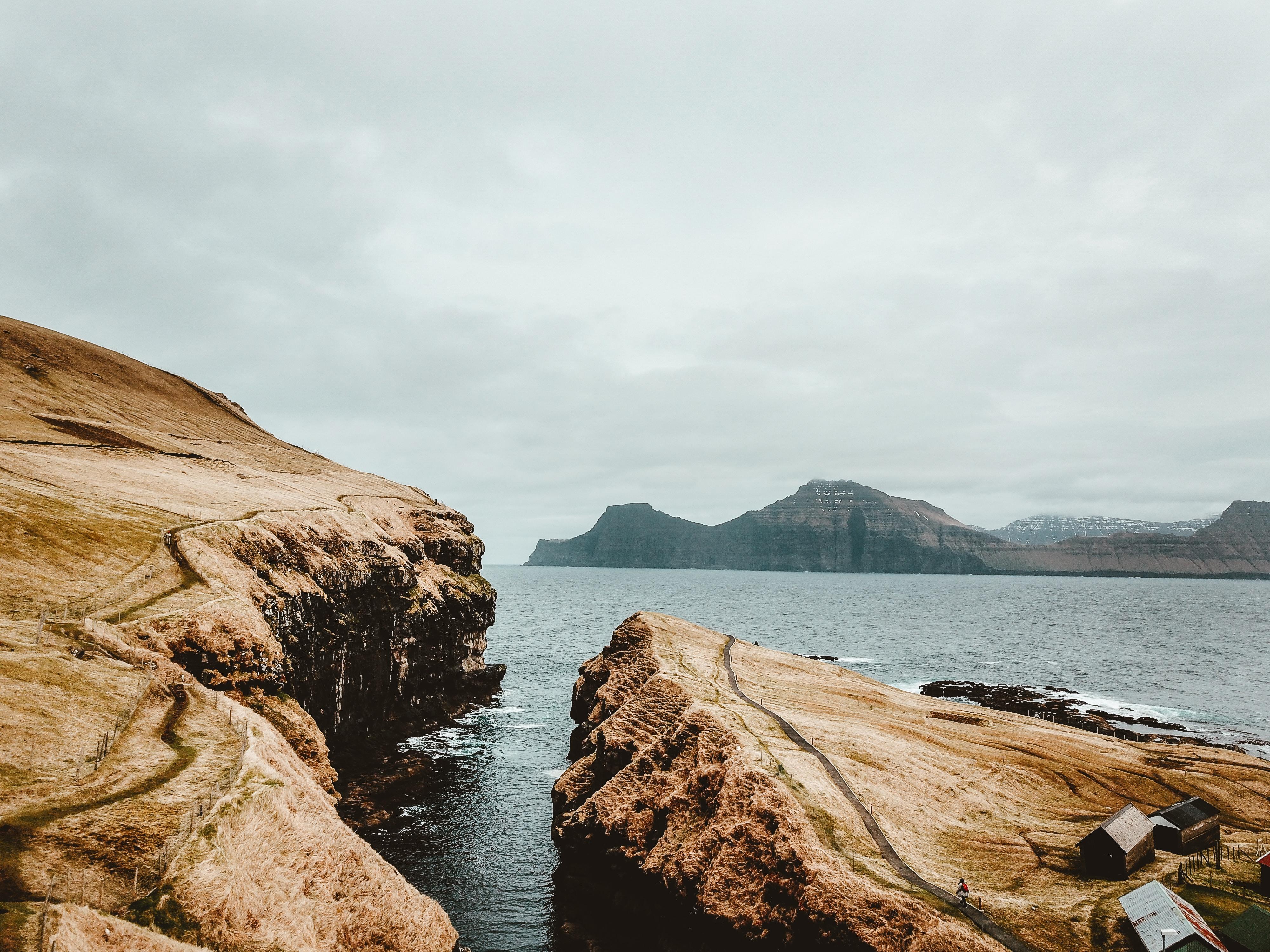 brown rock formation near body of water under blue sky