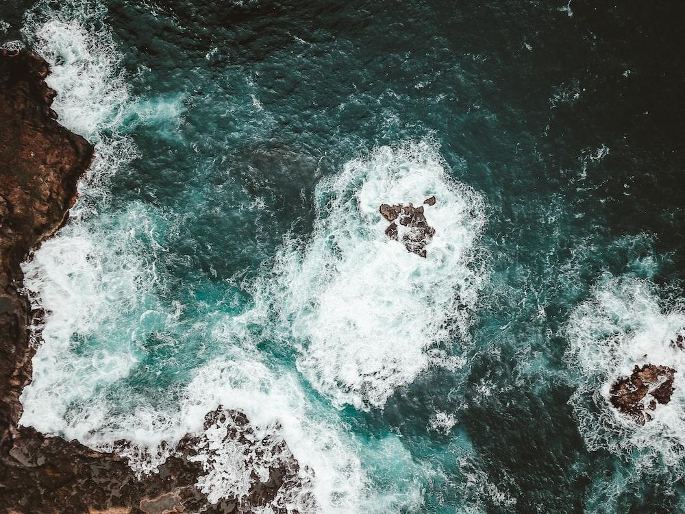 aerial photo of crashing waves through rocks