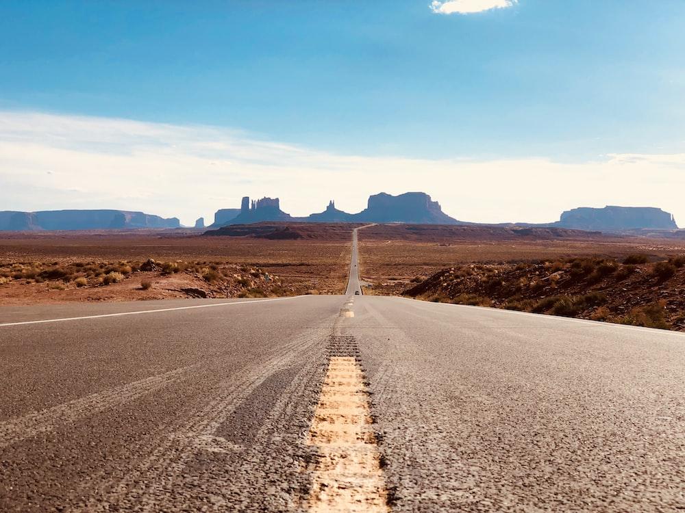 gray asphalt road in between sands