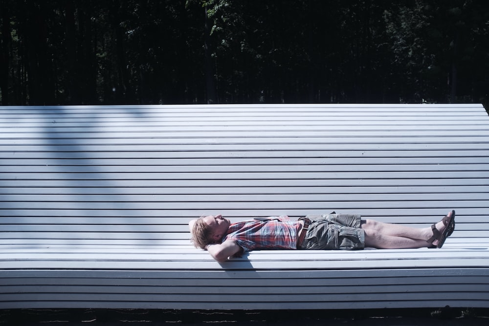 man lying on bench during daytime