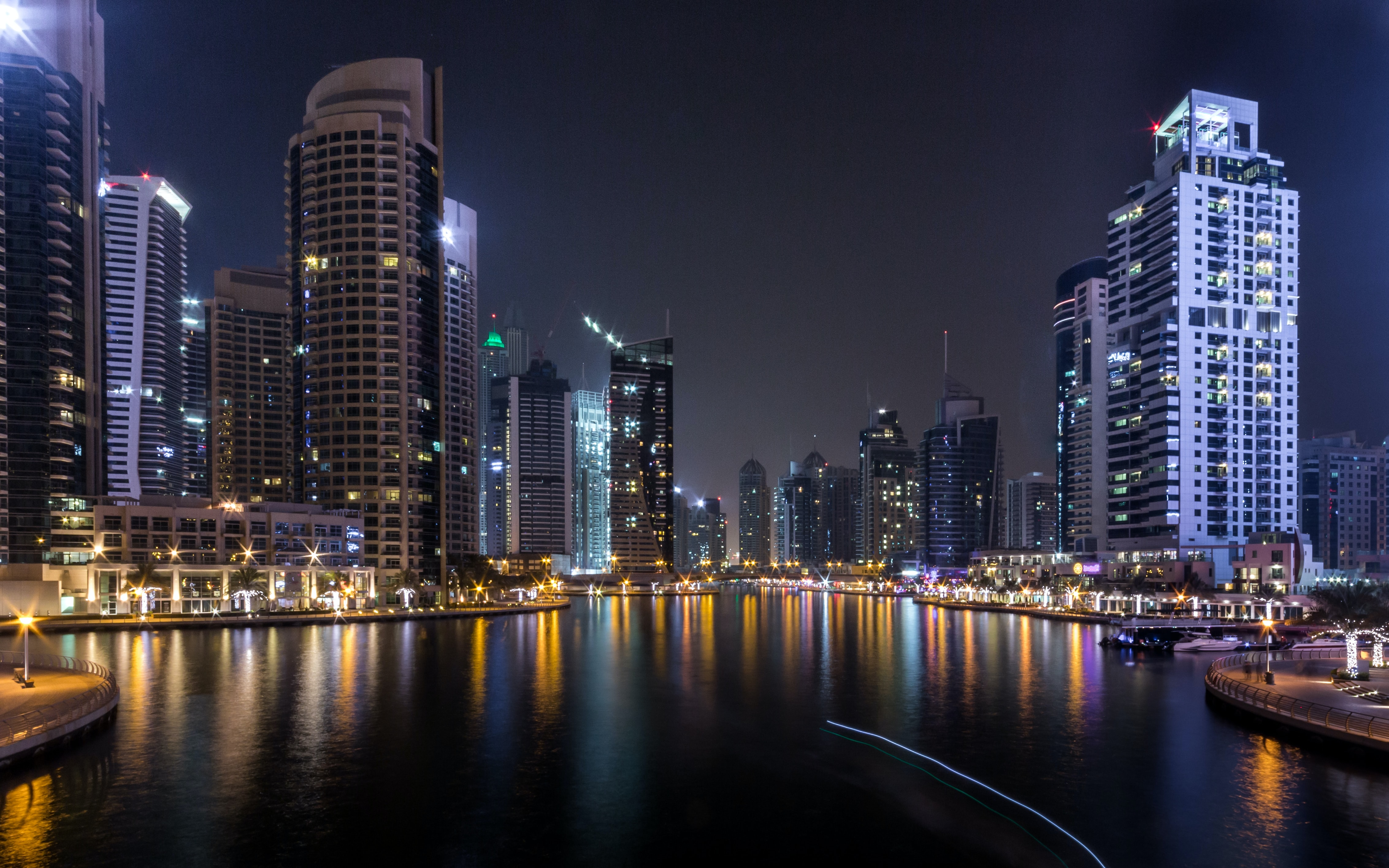 lighted city buildings beside body of water