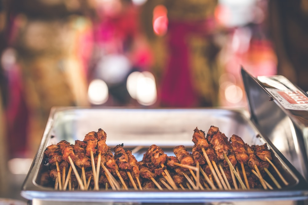 selective focus photography of skewered pork on tray