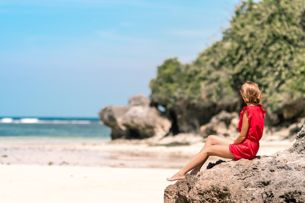 selective focus photo of woman sitting on rock formation seashore