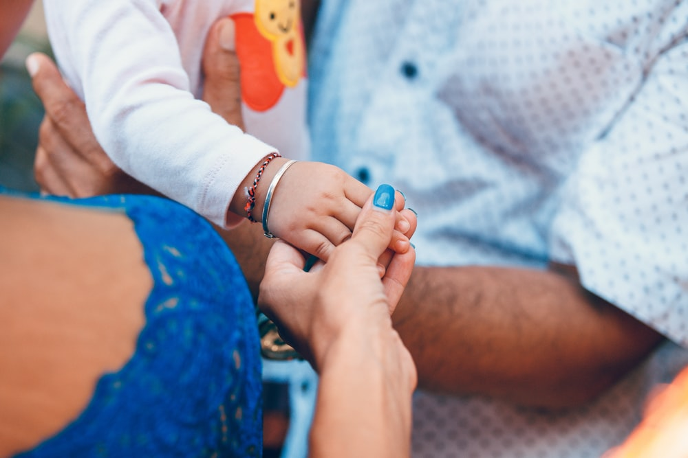 person holding child hand