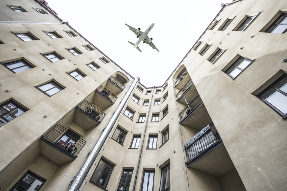 worm's-eye view photography of building and airplane