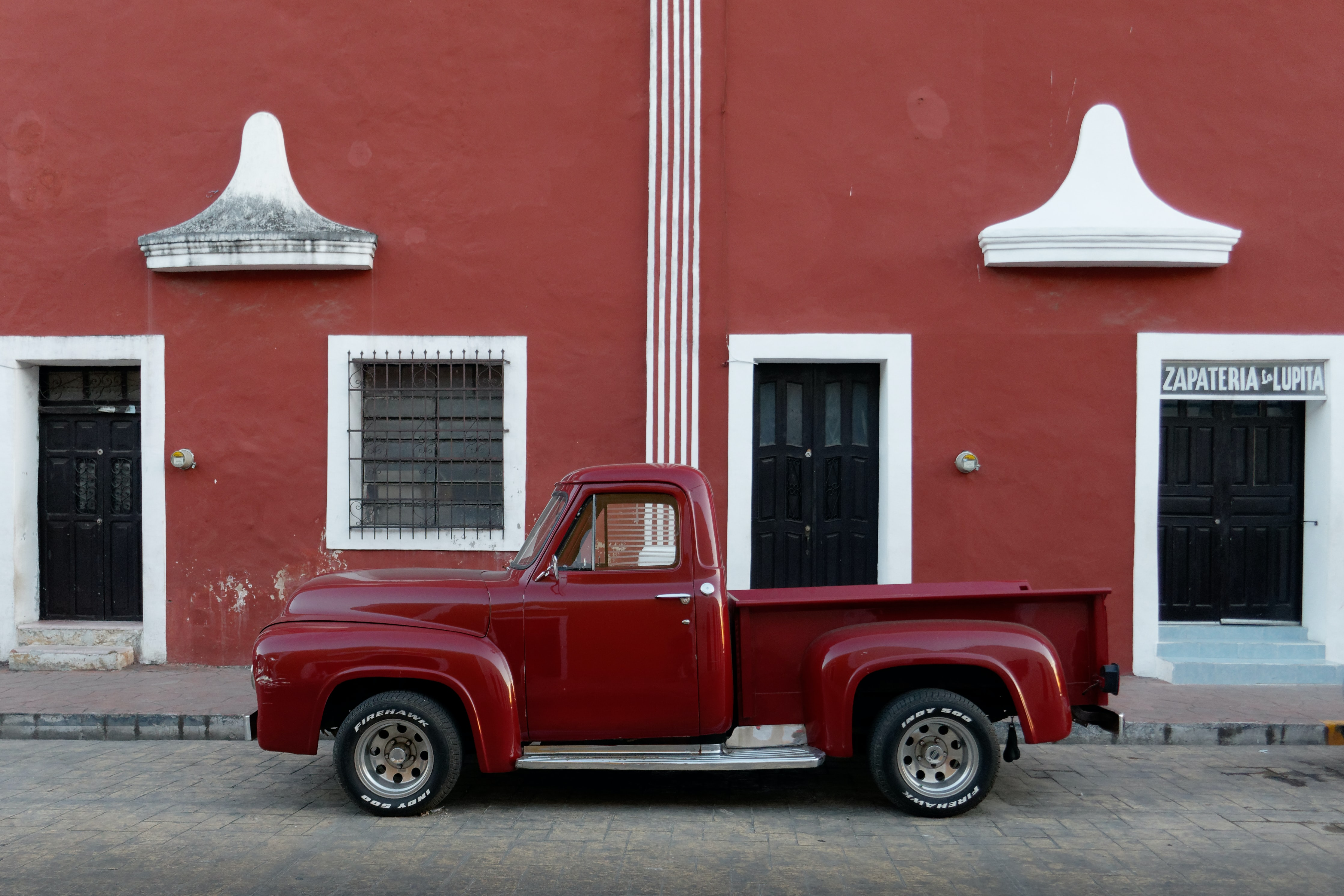 red single cab pickup truck parked outside brown builing