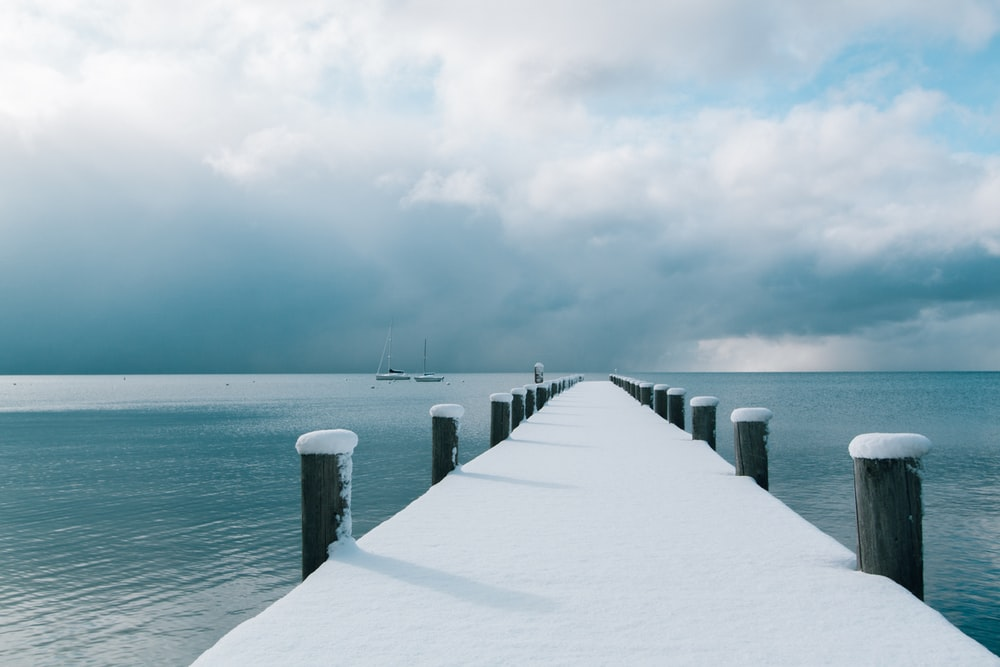 brown wooden dock covered with snow and body of water