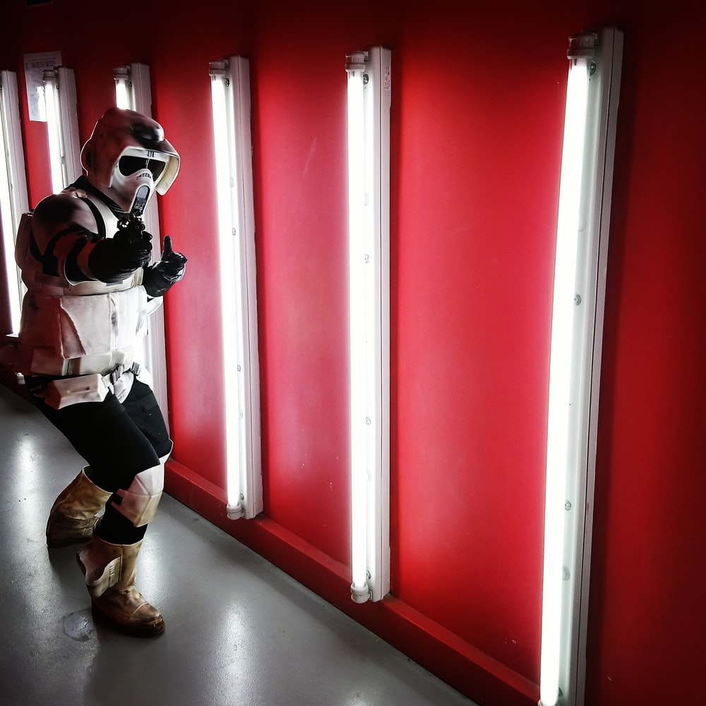 person wearing gas mask near fluorescent lamp