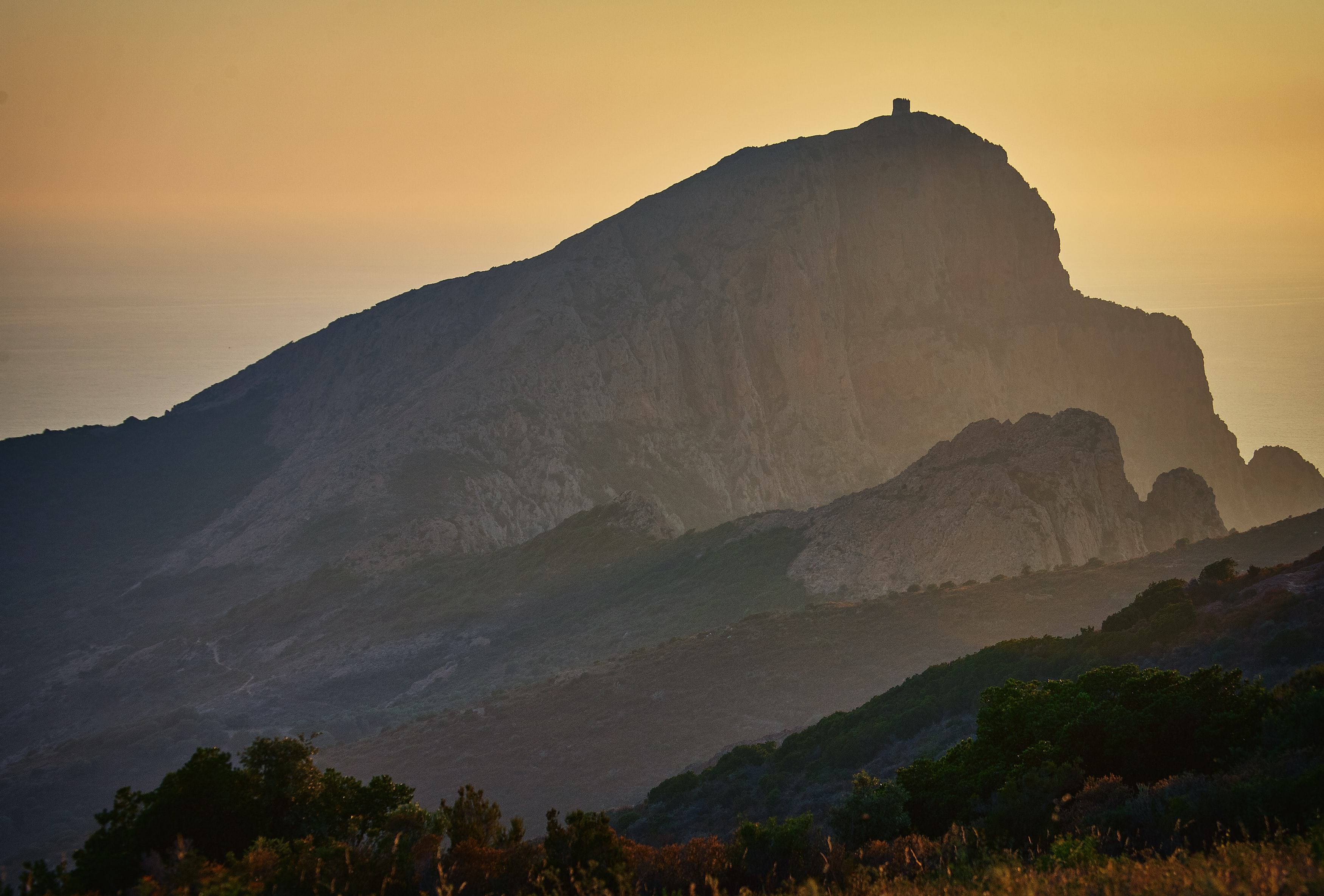 mountain covered with smoke during golden hour