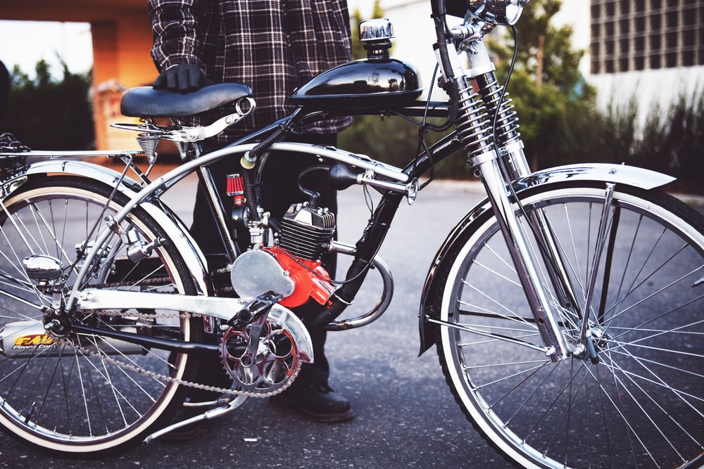 person holding black motorized bicycle