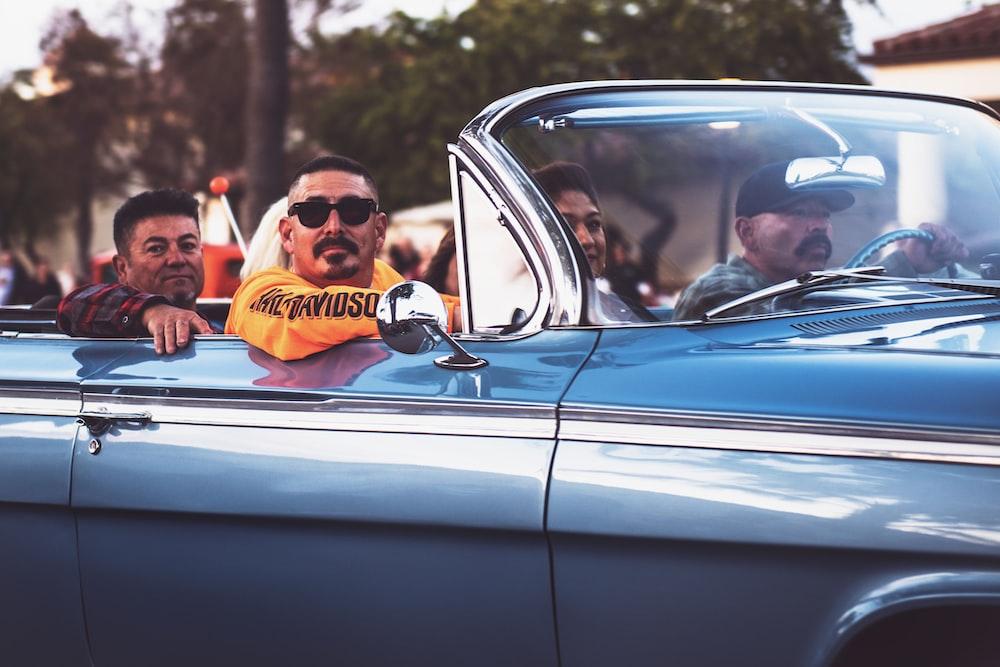 men ridding vintage convertible car