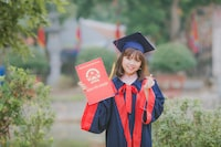 woman wearing black and red academic dress and mortar board holding red book cover near green grass