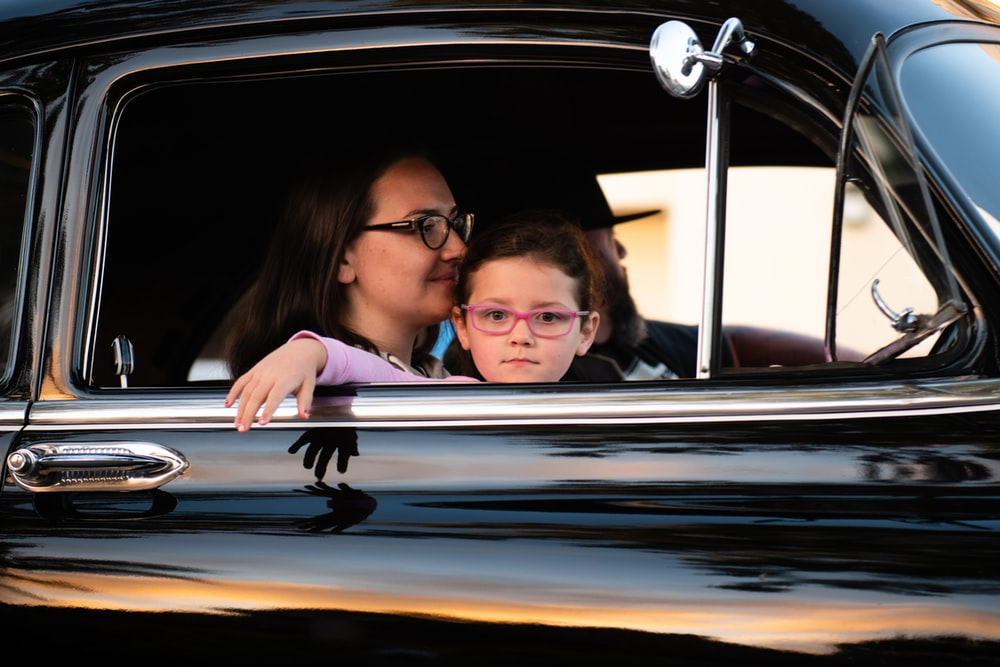 girl and woman inside black car