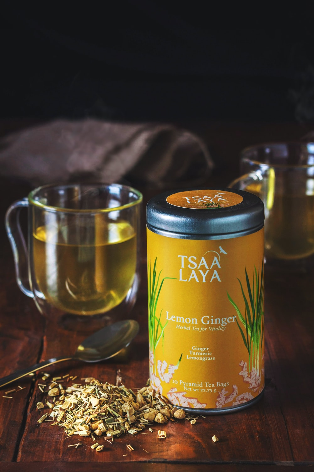 clear glass mug and Tsaa Laya lemon ginger labeled container on brown wooden table